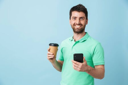 Image of excited young handsome bearded man posing isolated over blue wall background holding cup of coffee using mobile phone.