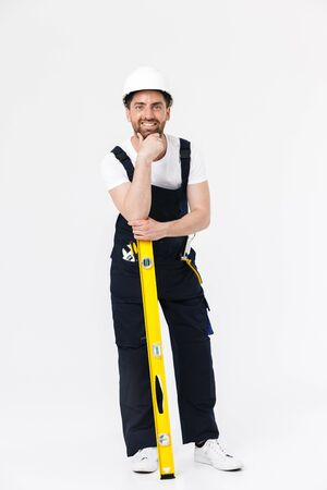 Full length portrait of a handsome bearded builder man wearing overalls standing isolated over white background, holding yellow level