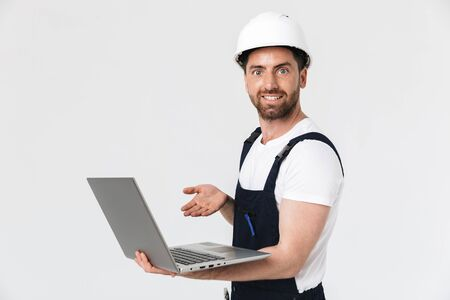Confident happy bearded builder man wearing overalls and hardhat standing isolated over white background, using laptop computer Stock Photo
