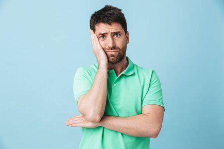 Image de fatigué ennuyé jeune bel homme barbu posant isolé sur fond de mur bleu.