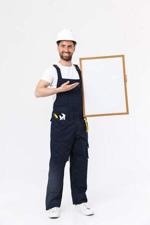 Full length of a confident bearded builder man wearing overalls and hardhat standing isolated over white background, showing blank board