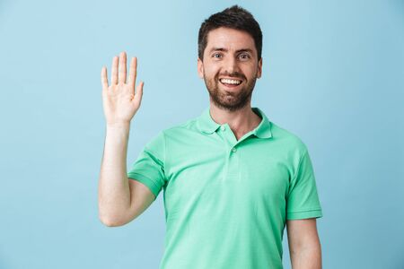Image of a happy young handsome bearded man posing isolated over blue wall background looking camera waving to you. 스톡 콘텐츠