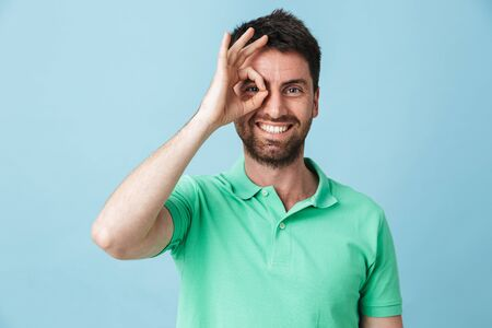 Image of a happy young handsome bearded man posing isolated over blue wall background looking camera showing okay gesture.