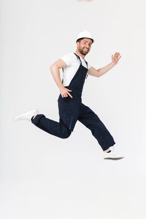 Full length of a confident bearded builder man wearing overalls and hardhat jumping isolated over white background