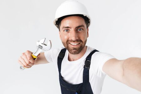 Confident bearded builder man wearing overalls and hardhat standing isolated over white background, showing adjustable wrench, taking a selfie 스톡 콘텐츠