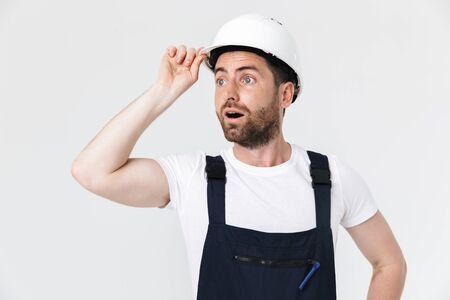 Confident bearded builder man wearing overalls and hardhat standing isolated over white background, looking away