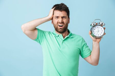 Image of shocked confused young handsome bearded man posing isolated over blue wall background holding alarm clock. Stock fotó