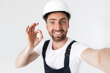Confident bearded builder man wearing overalls and hardhat standing isolated over white background, taking a selfie