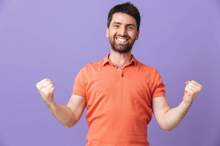 Image of a happy young handsome bearded man posing isolated over violet purple wall background make winner gesture. 스톡 콘텐츠