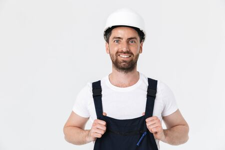 Confident bearded builder man wearing overalls and hardhat standing isolated over white background