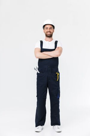 Full length of a confident bearded builder man wearing overalls and hardhat standing isolated over white background, arms folded