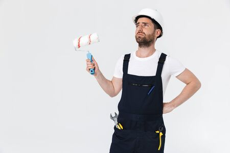 Portrait of a handsome bearded builder man wearing overalls standing isolated over white background, holding paint brush Imagens