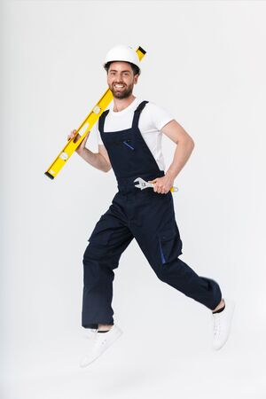 Full length of a confident bearded builder man wearing overalls and hardhat walking isolated over white background, carrying measurement level