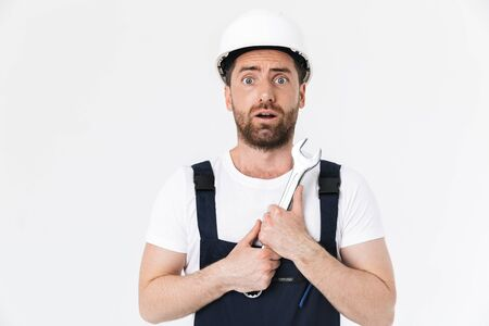 Confident bearded builder man wearing overalls and hardhat standing isolated over white background, showing adjustable wrench Imagens