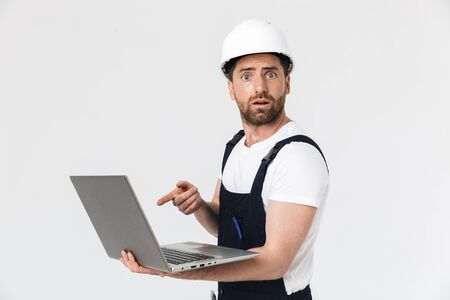 Confused bearded builder man wearing overalls and hardhat standing isolated over white background, holding laptop computer