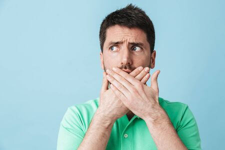 Image of scared confused young handsome bearded man posing isolated over blue wall background covering mouth.