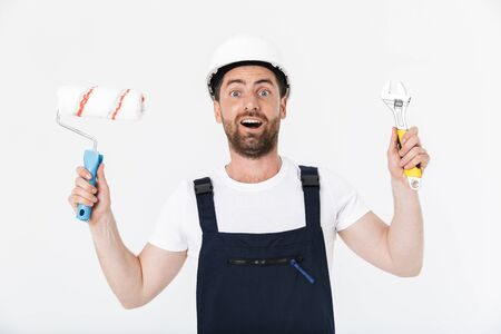 Confident bearded builder man wearing overalls and hardhat standing isolated over white background, showing wrench