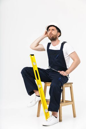 Full length of a tired bearded builder man wearing overalls and hardhat sitting on a chair isolated over white background