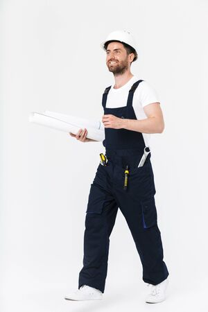 Full length of a confident bearded builder man wearing overalls and hardhat standing isolated over white background, carrying paper draft