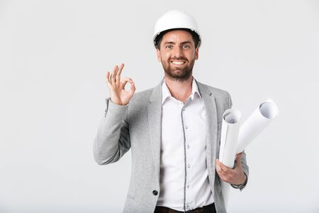 Confident bearded man builder wearing suit and hardhat standing isolated over white background, carrying blueprints, showing ok Imagens