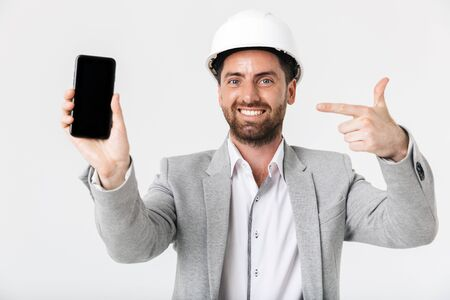 Confident bearded man builder wearing suit and hardhat standing isolated over white background, showing blank screen mobile phone Imagens