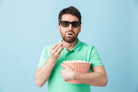 Portrait of a handsome bearded man wearing casual clothing standing isolated over blue background, eating popcorn while watching movie