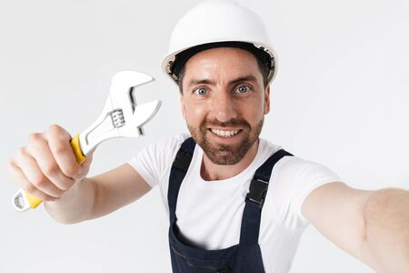 Confident bearded builder man wearing overalls and hardhat standing isolated over white background, showing adjustable wrench, taking a selfie Imagens