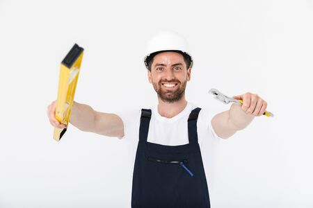 Confident bearded builder man wearing overalls and hardhat standing isolated over white background, showing wrench and measurement level