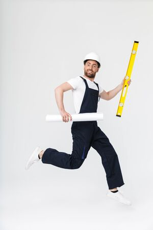 Full length of a confident bearded builder man wearing overalls and hardhat jumping isolated over white background, holding blueprint and measurement level