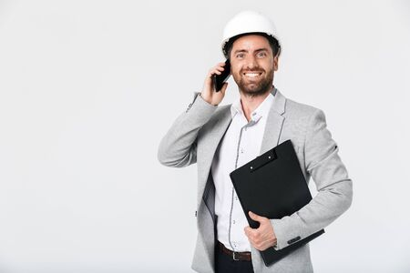 Confident bearded man builder wearing suit and hardhat standing isolated over white background, talking on mobile phone Imagens