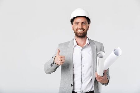 Confident bearded man builder wearing suit and hardhat standing isolated over white background, carrying blueprints, thumbs up Imagens