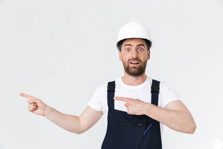 Confident bearded builder man wearing overalls and hardhat standing isolated over white background, pointing finger at copy space
