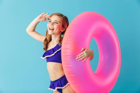Cheerful little girl wearing swimsuit standing isolated over blue background, playing with inflatable ring