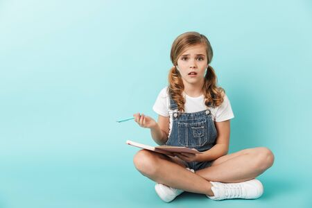 Portrait of a little girl isolated over blue background, writing in a notebook