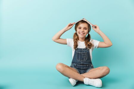 Portrait of a cheerful little girl sitting isolated over blue background, holding book on her head