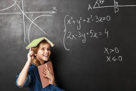 Image of pretty happy young little school girl posing isolated over chalkboard wall background.