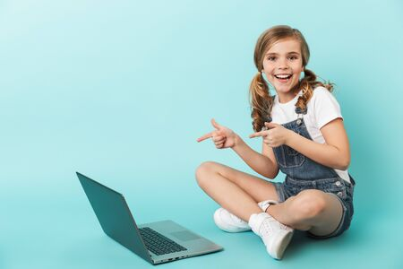 Portrait of a cheerful little girl isolated over blue background, studying with laptop computer, pointing finger