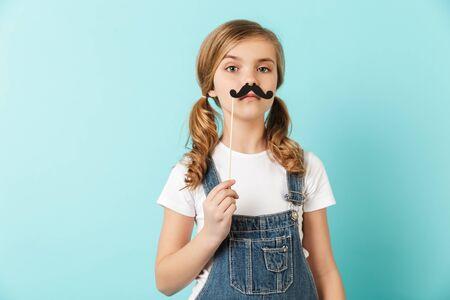 Porträt eines fröhlichen kleinen Mädchens auf blauem Hintergrund isoliert, das Spaß mit gefälschtem Schnurrbart hat