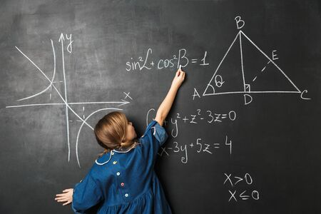 Smart little schoolgirl standing at the blackboard with math graphics, writing on it