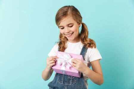 Portrait of a cheerful little girl isolated over blue background, showing present box Stock Photo