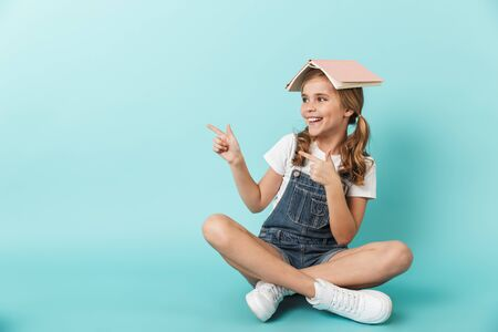 Portrait of a cheerful little girl sitting isolated over blue background, holding book on her head, pointing away