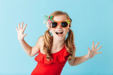 Cheerful little girl wearing swimsuit standing isolated over blue background, posing in sunglasses