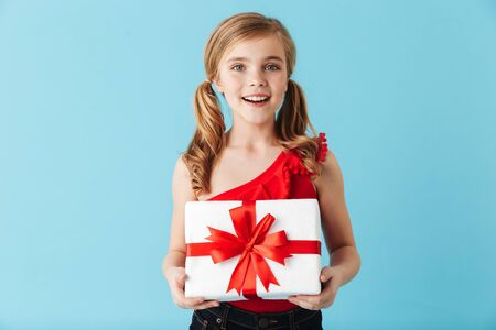 Cheerful little girl wearing swimsuit standing isolated over blue background, holding present box