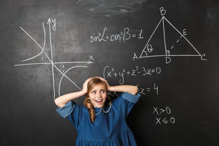 Image of pretty shocked confused young little school girl posing isolated over chalkboard wall background.