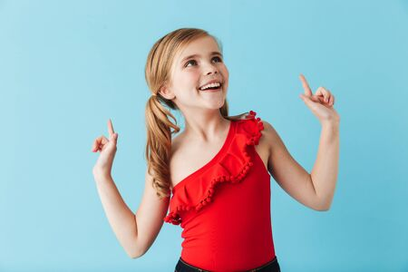 Cheerful little girl wearing swimsuit standing isolated over blue background, pointing at copy space Фото со стока
