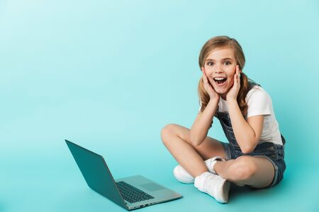 Portrait of a cheerful little girl isolated over blue background, studying with laptop computer