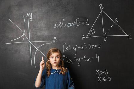 Smart little schoolgirl standing at the blackboard with math graphics written on it Banco de Imagens