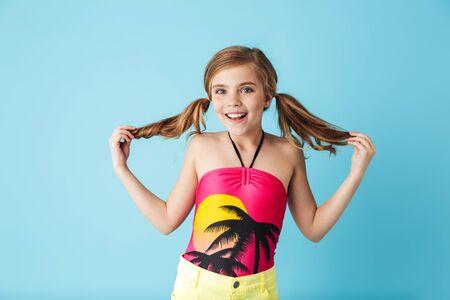 Fröhliches kleines Mädchen im Badeanzug, das isoliert auf blauem Hintergrund steht und Spaß hat