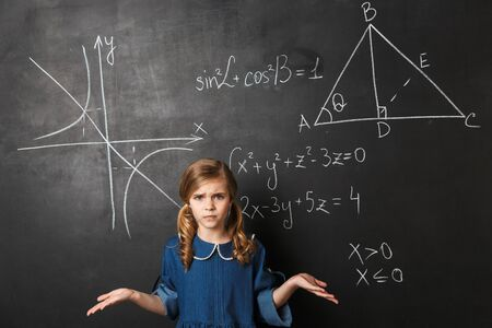 Confused little schoolgirl standing at the blackboard with math graphics written on it Banco de Imagens