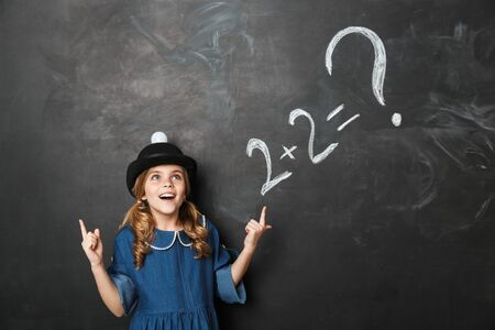 Image of pretty happy young little school girl posing isolated over chalkboard wall background have an idea.